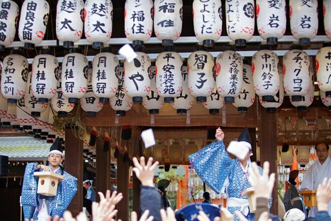 Temple monks and workers throwing beans to people during the Setsubun rituals at Yasaka Shrine