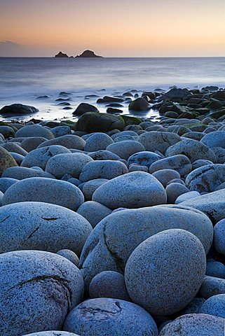Circular boulders at Porth Nanven beach, with The Brisons island on the horizon, Cornwall, England, United Kingdom, Europe