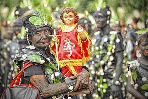 Old woman holding a Santo Nino figur, Ati Atihan festival, Kalibo, Aklan, Panay Island, Visayas, Philippines