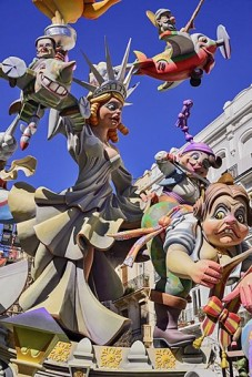 Spain, Valencia Province, Valencia, Papier Mache figure of a woman resembling the Statue of Liberty with various other figures flying around her during Las Fallas festival.