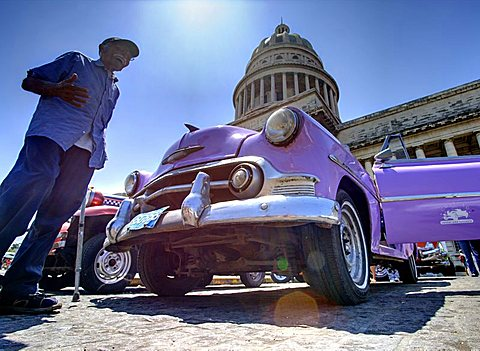 Low angle shot of The Capitolio with classic American car and old man in foreground, Havana, Cuba, West Indies, Caribbean, Central America