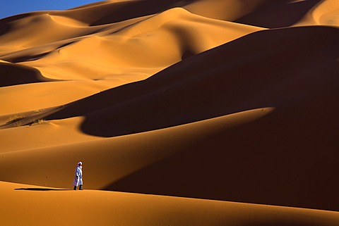 Berber man walking among the orange sand dunes of the Erg Chebbi sand sea, Sahara Desert near Merzouga, Morocco, North Africa, Africa