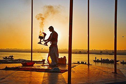 INDIA Uttar Pradesh Varanasi Performing the Ganga Aarti Ceremony at dawn over the River Ganges. India Varanasi Uttar Pradesh Aarti Ceremony River Ganges Faith Hindu Hinduism Tradition Dawn Perform Holy Sacred Sunrise Travel Tourism Holidays Asia Sub-Contin