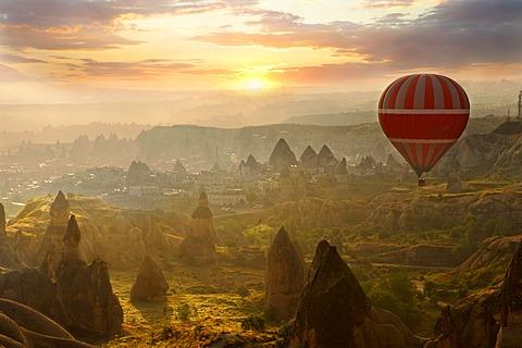 Hot air balloon over volcanic tuff rock formations at dawn, Goreme, Cappadocia, Turkey
