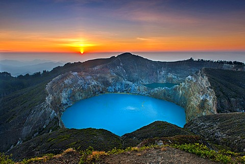 Sunrise over Tiwu Ko'o Fai Nuwa Muri, one of three crater lakes on the summit of Mount Kelimutu on Flores island, Indonesia.