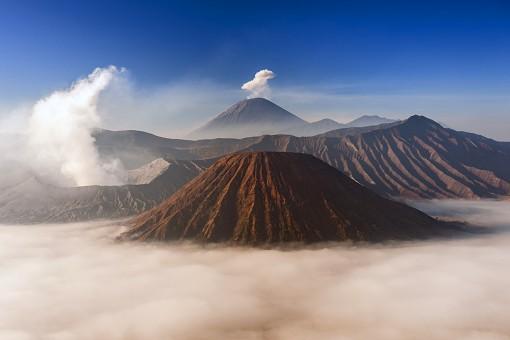 Mount Bromo (venting steam, left) and Gunung Semeru (centre background) in Bromo Tengger Semeru National Park, Java, Indonesia.