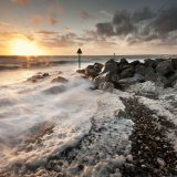 Gale driven surf and foam pile onto a shingle beach at sunset at Dinas Dinlle, Llyn Peninsula, Gwynedd, Wales, United Kingdom, Europe