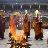 Fire ritual at chiwang monastery during the mani rimdu festival. these monks circumambulate the pyre after its ignition. one holds a long book wrapped in a felicitous scarf. the purifying fire takes the offering and raises them towards the sky in smoke. the circumambulatory ritual also recalls the way disciples showed respect for the buddhas body. solu khumbu, nepal