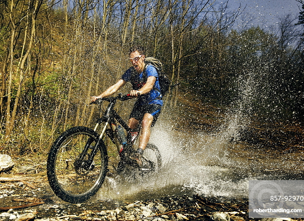Guy rides his mountain bike over mountain stream. Image captured at the moment of a biggest splash. Taken on Gledic mountains near Kragujevac, Central Serbia at a sunny Spring day.