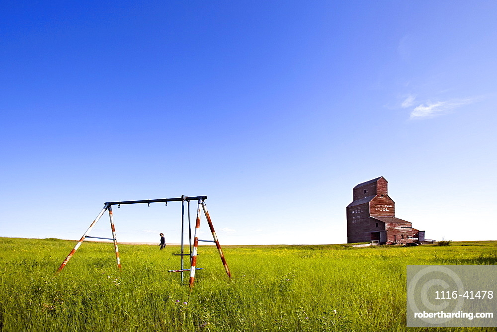 A Man Walking Through A Field With An Old Swing Set And An Old Grain Elevator, Bents, Saskatchewan, Canada