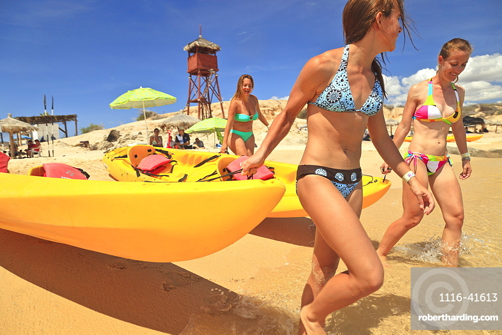 Young women pull a boat into the water from the beach at cabo pulmo, Baja california sur mexico