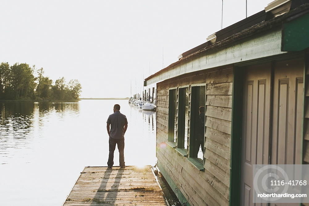 A man standing on the edge of a dock looking out over the ocean, White rock british columbia canada