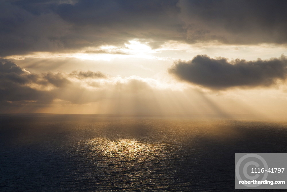 Sunlight streaming through the dark clouds and reflecting on the ocean, County clare, ireland