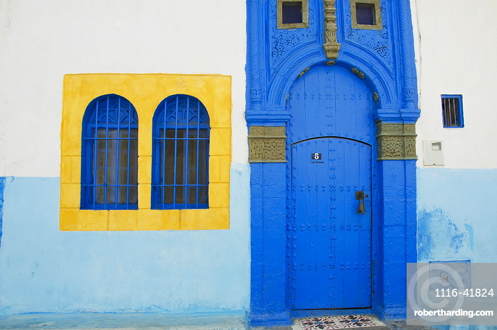 A painted blue door and bright yellow window frame on a house in old town, Rabat morocco