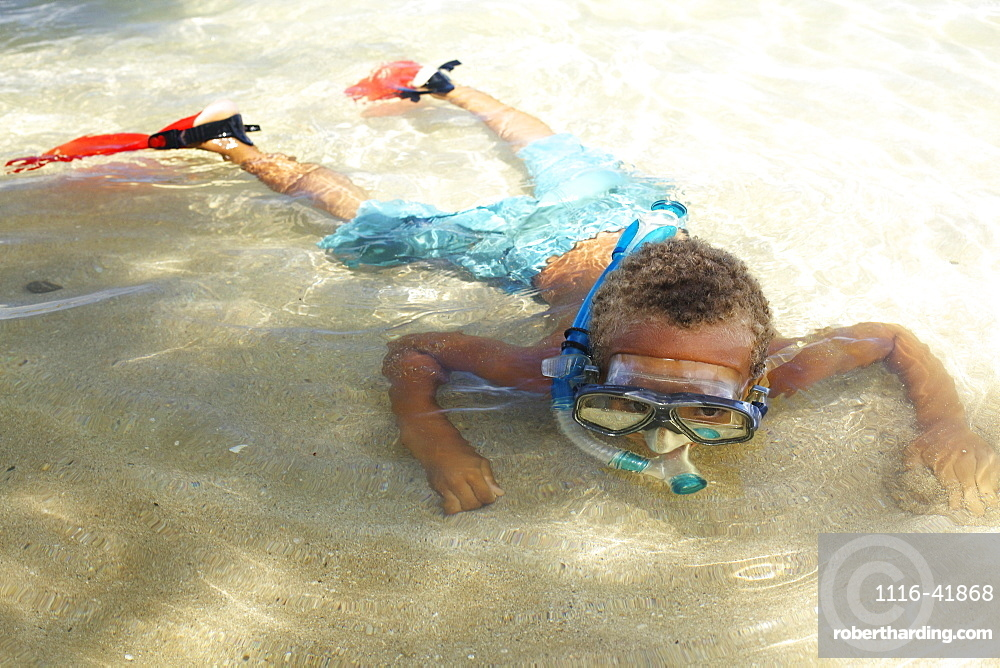 A young boy in the shallow water of the ocean with snorkelling gear, Hawaii united states of america