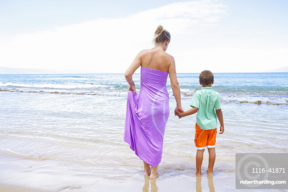 A mother and son hold hands while standing in the shallow water at the ocean, Hawaii united states of america