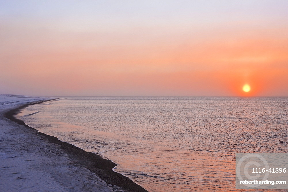 Sunset through windblown snow creates a sundog above the Beaufort Sea along the coast just outside of Barrow, Winter, Arctic Alaska, USA.