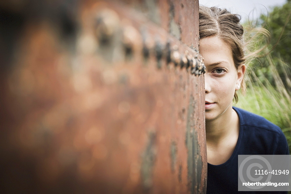 A young woman poses while peering out from behind a rusty weathered drum, South naknek bristol bay alaska united states of america