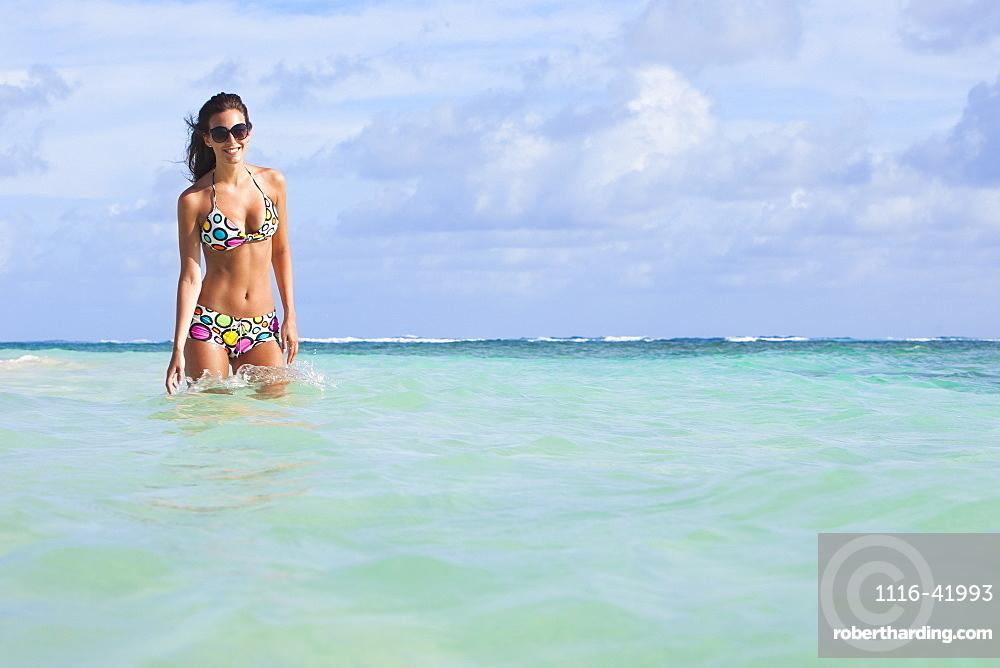 A Woman Standing In The Ocean Wearing A Colourful Bikini And Sunglasses, Punta Cana, La Altagracia, Dominican Republic