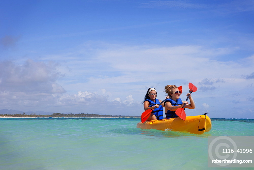 Two Women In Lifejackets Paddling In A Yellow Boat, Punta Cana, La Altagracia, Dominican Republic