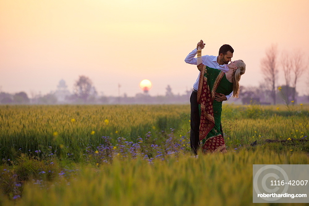 Portrait Of A Mixed Race Couple Her Wearing A Sari In A Field At Sunset, Ludhiana, Punjab, India