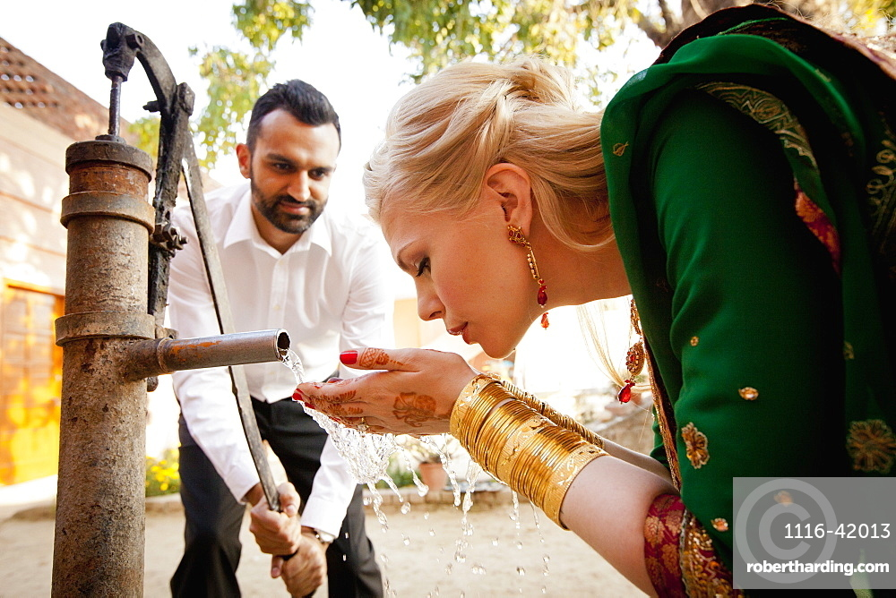 A Man Pumping Water From A Well As A Blond Woman In A Sari Drinks From Her Cupped Hands, Ludhiana, Punjab, India
