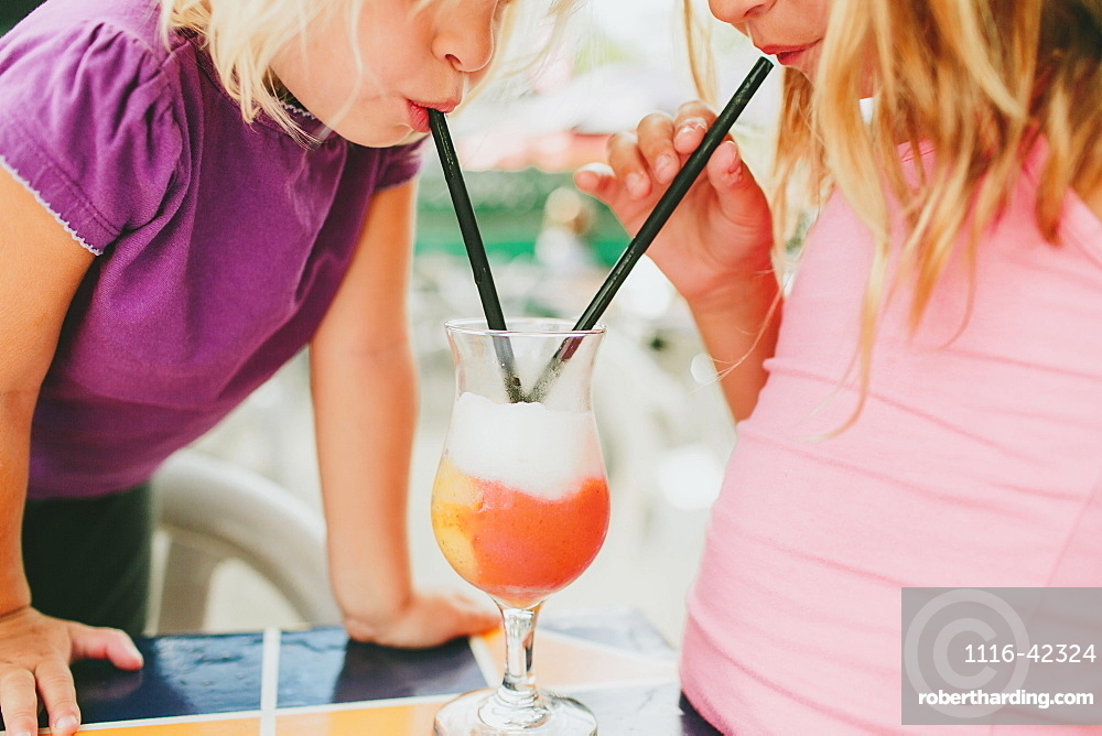 Two Young Girls Share A Drink With Straws, Peachland, British Columbia, Canada
