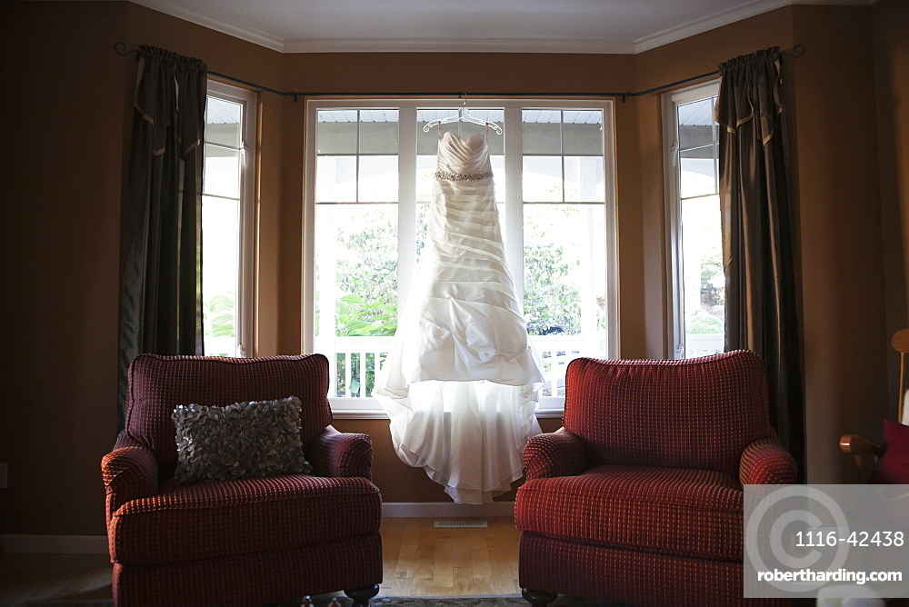 A Wedding Dress Hanging In The Window Of A Home, British Columbia, Canada