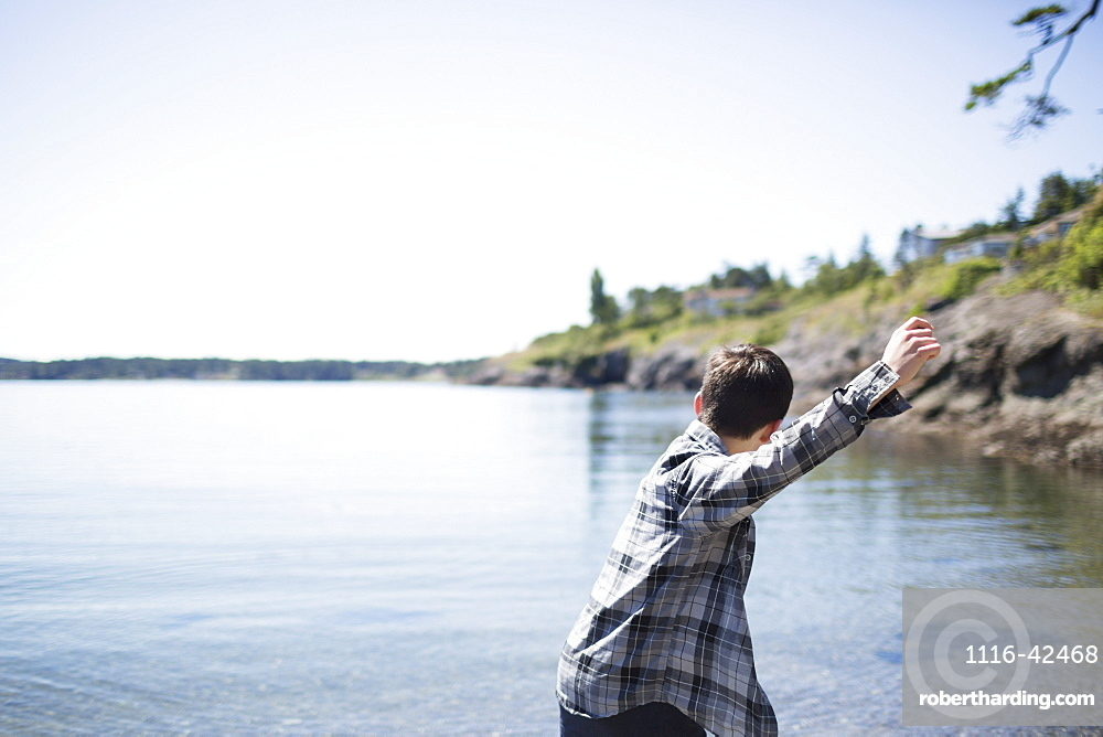 A Boy Throws Rocks Into The Water, Victoria, British Columbia, Canada