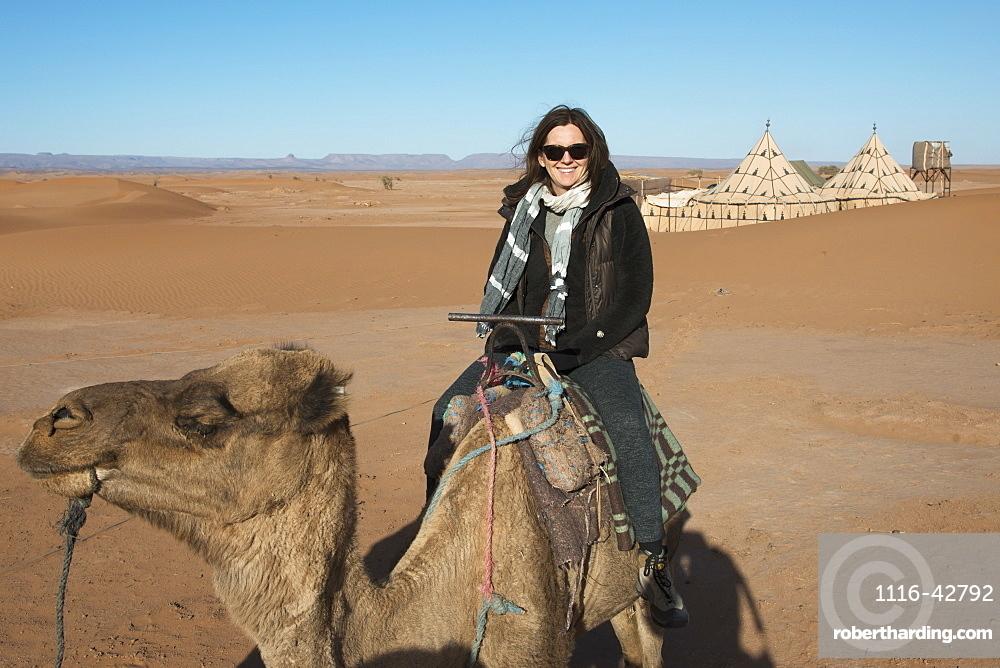 A woman riding a camel on the erg chegaga dunes, Souss-massa-draa morocco