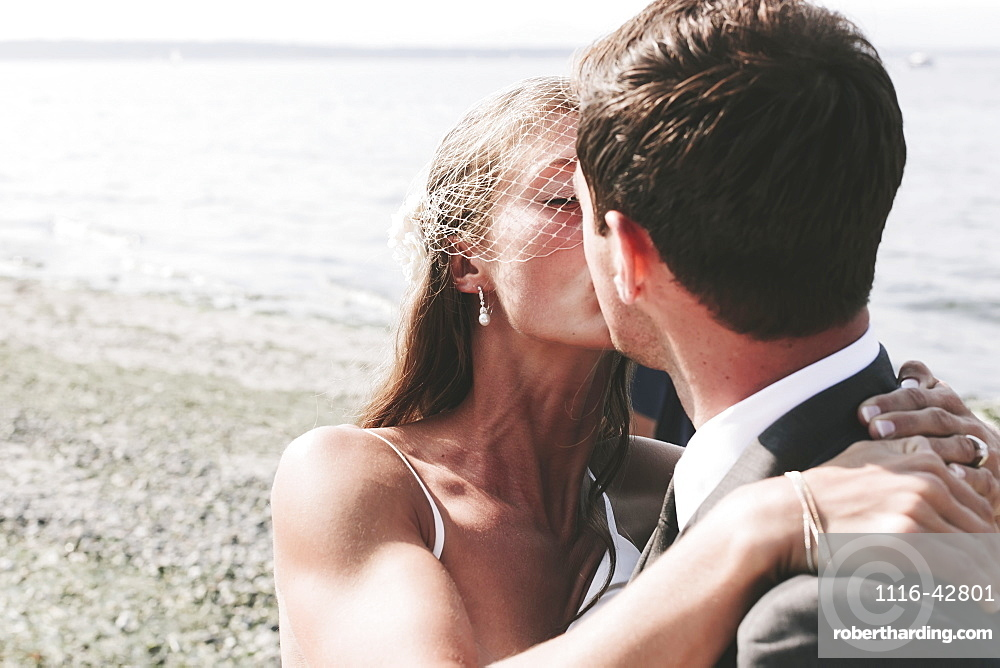 A bride and groom kissing on a beach at the water's edge, Kirkland washington united states of america