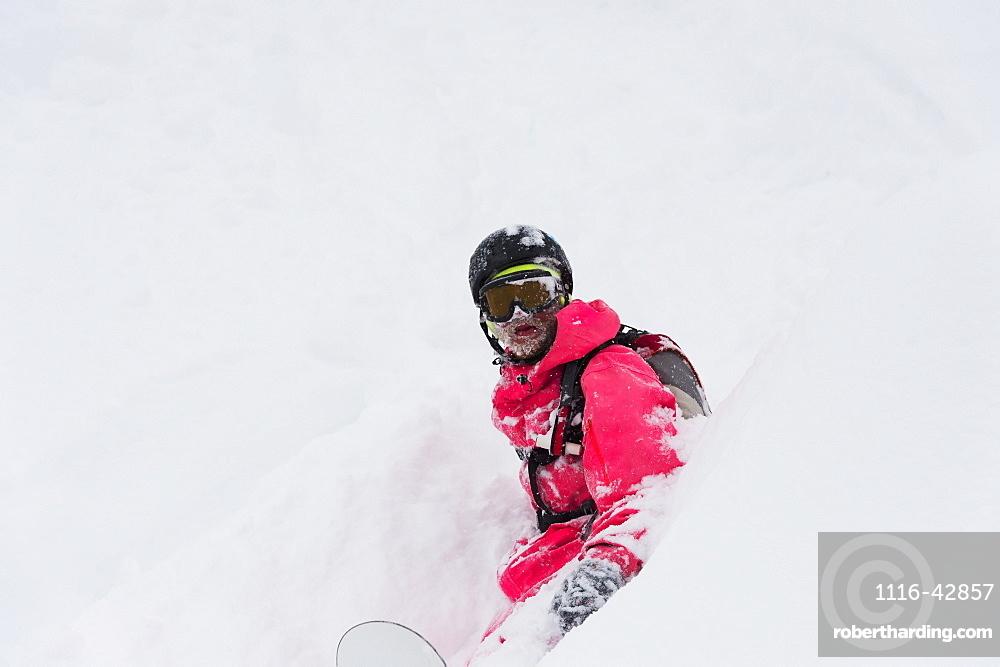 Snowboarder Sitting In Deep Powder Snow, St. Moritz, Graubunden, Switzerland