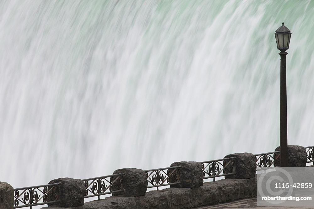 Railing And Lamp Post With The Horseshoe Falls In The Background At Table Rock, Niagara Falls, Ontario, Canada