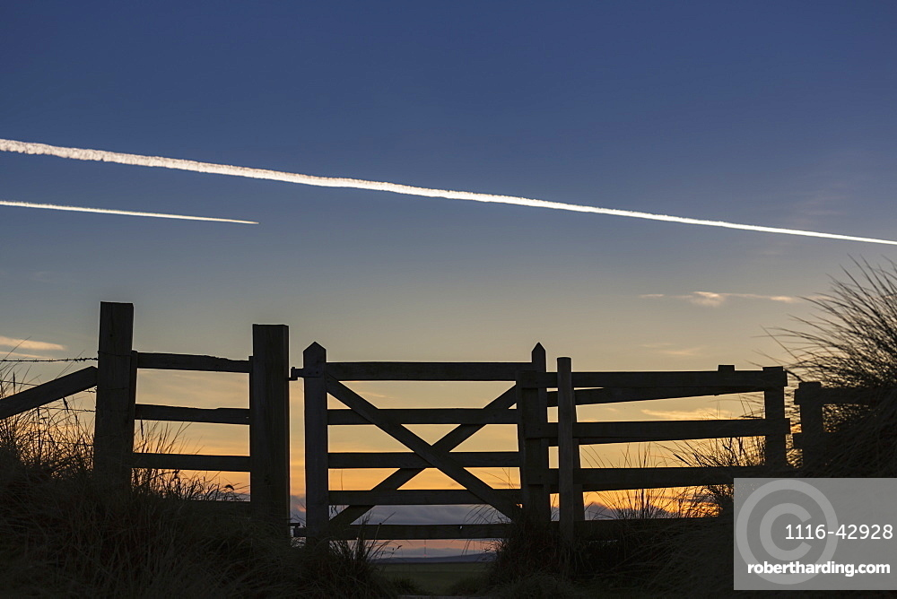 Silhouette Of A Fence At Sunset With Jet Vapour In The Sky, Northumberland, England