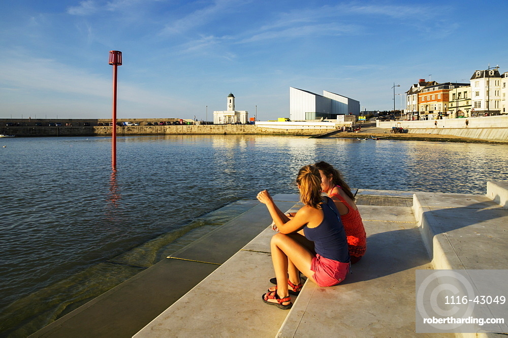 Teenage Girls Sitting On Steps Along The Waterfront, Margate, Kent, England