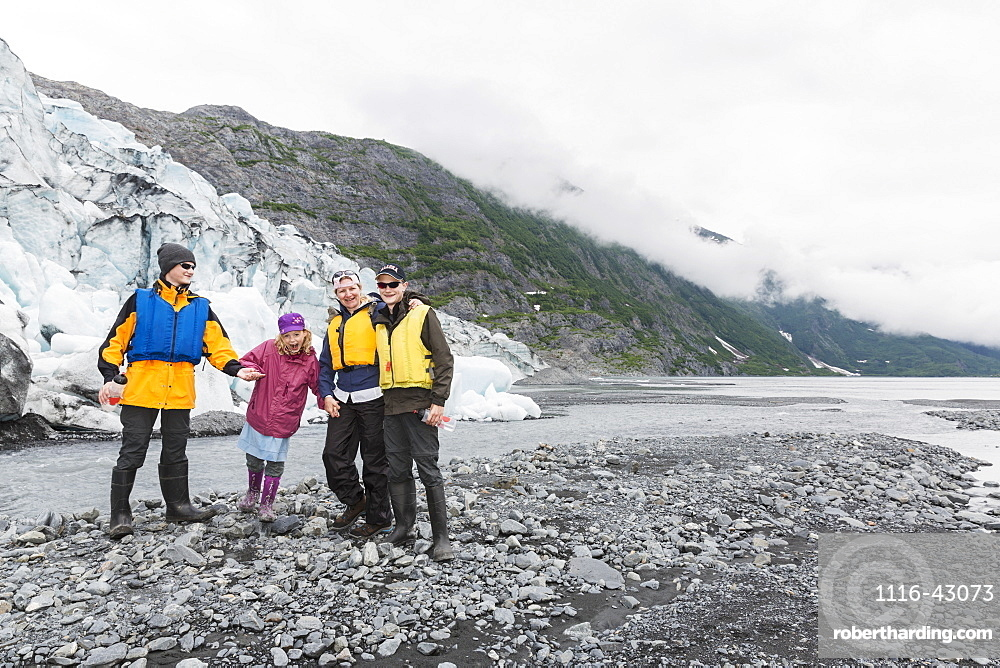 A Family Poses In Front Of Shoup Glacier And Chugach Mountains, Shoup Bay State Marine Park, Prince William Sound, Valdez, Alaska, United States Of America