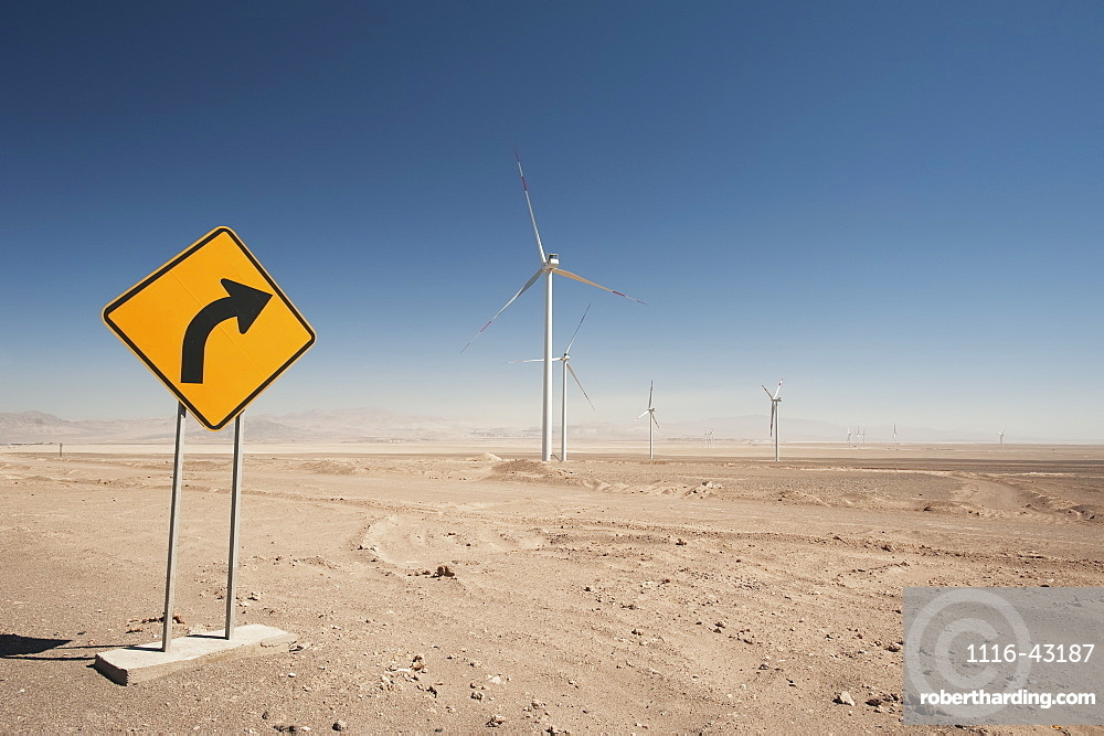 Wind Turbines In The Atacama Desert With A Yellow Sign Indicating A Curve, Calama, Chile