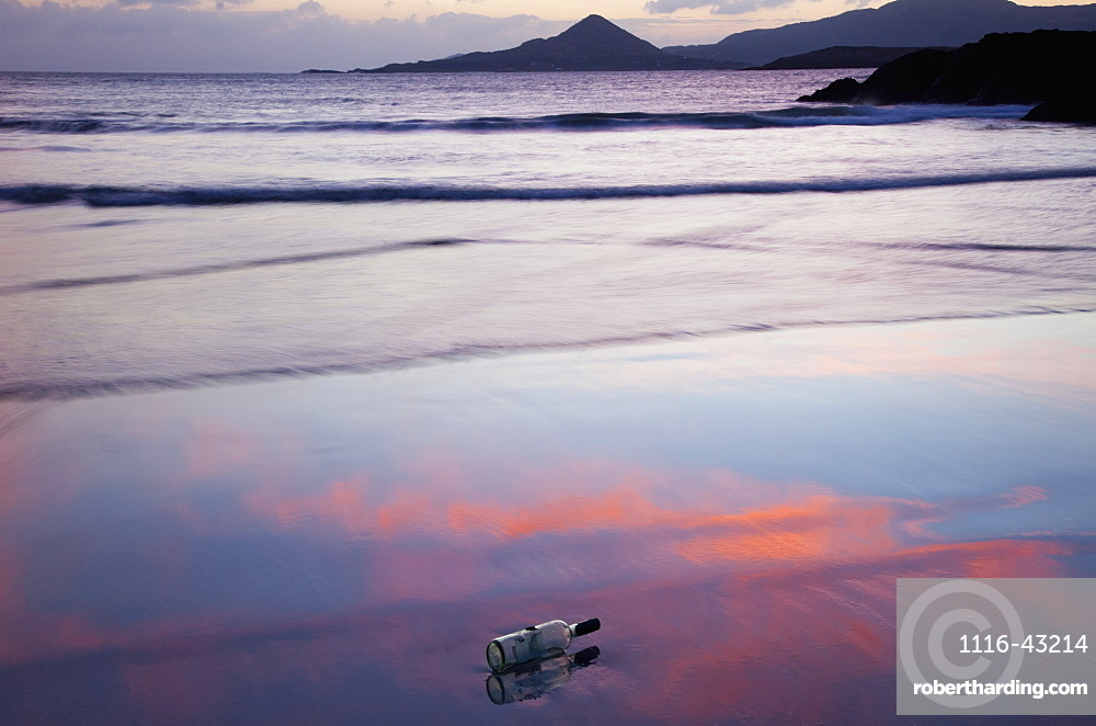A Glass Bottle Lays On The Wet Sand At The Water's Edge At Sunset, County Kerry, Ireland