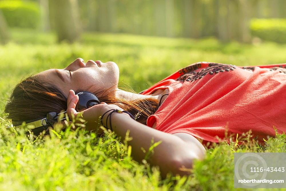 Chinese Girl Listening To Music On The Grass, Xiamen, Fujian Province, China
