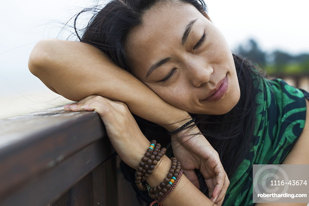 A Young Woman Lays Her Head Against A Wooden Railing At The Beach, Jincheng, Kinmen, Taiwan