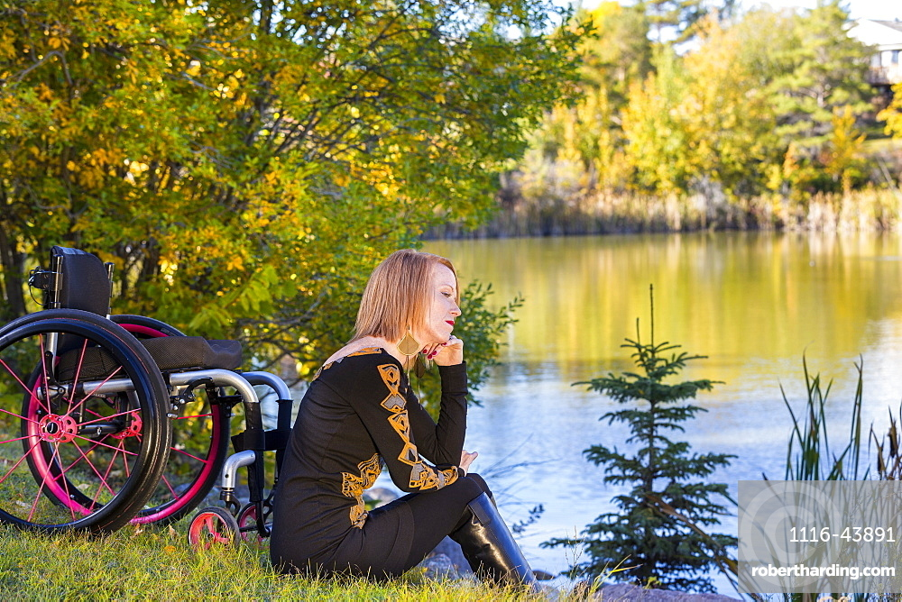 Young Disabled Woman Sitting Beside Her Wheelchair In A City Park In Autumn, Edmonton, Alberta, Canada