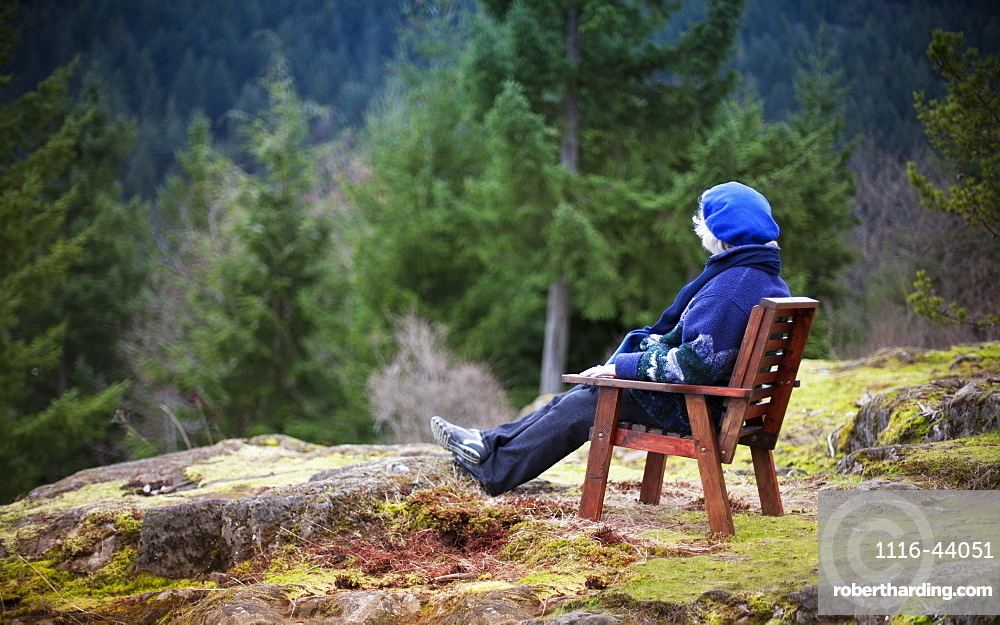 Woman Sitting In A Chair Looking At Nature, Bowen Island, British Columbia, Canada