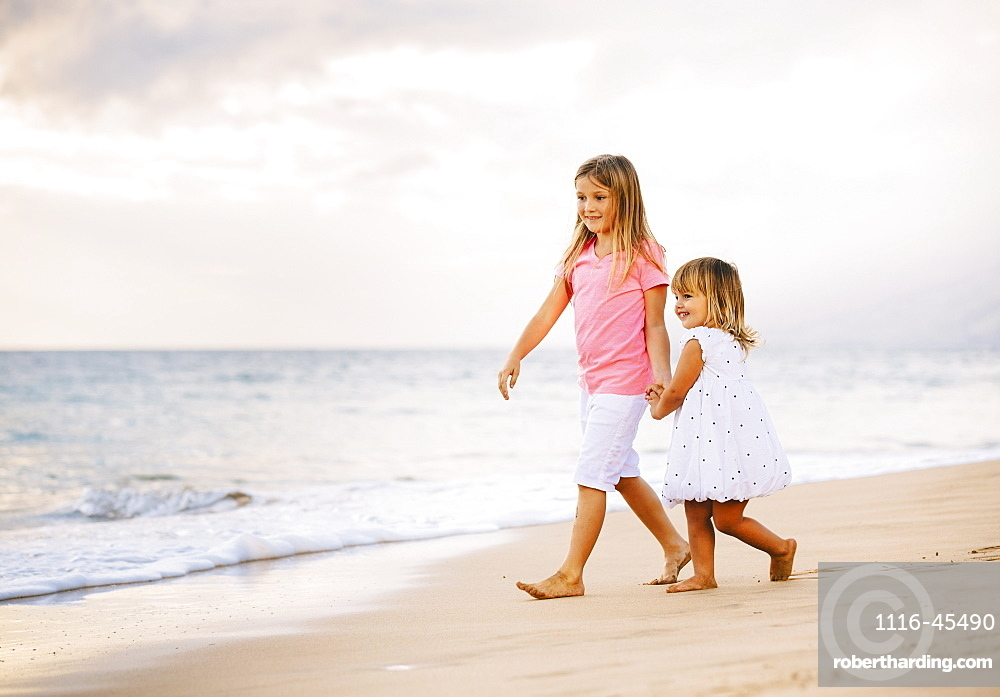 Adorable Young Sisters, Two Little Girls Walking Together On The Beach At Sunet, Family Lifestyle.