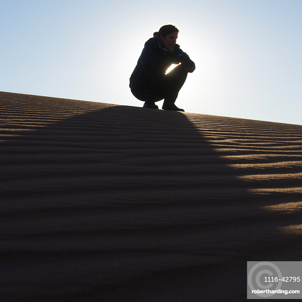 A woman crouching on the top of a sand dune, Souss-massa-draa morocco