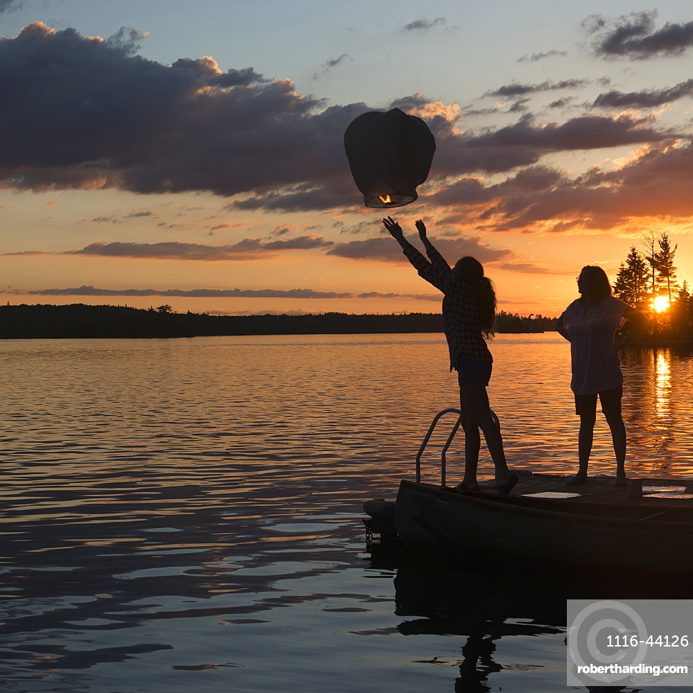 Silhouette Of A Teenage Girl Releasing A Lit Lantern Out Over A Lake At Sunset, Lake Of The Woods, Ontario, Canada