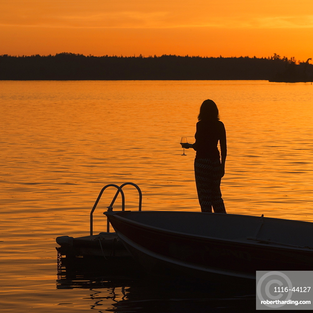 Silhouette Of A Woman Holding A Glass Of Wine While Standing On A Dock On A Golden Lake At Sunset, Lake Of The Woods, Ontario, Canada