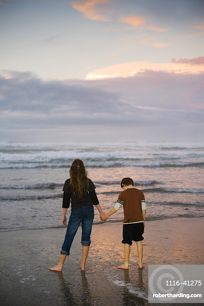 A Mother And Son Hold Hands On A Beach Looking Out At The Water