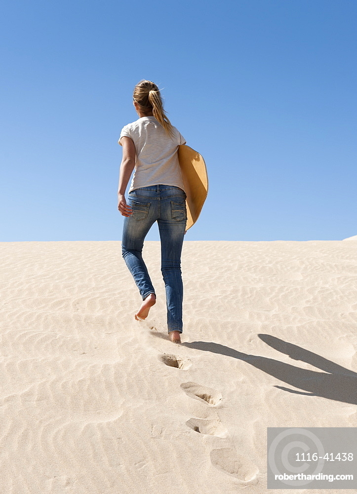 A Young Woman Walks With A Board Over The Punta Paloma Sand Dunes, Tarifa, Cadiz, Andalusia, Spain