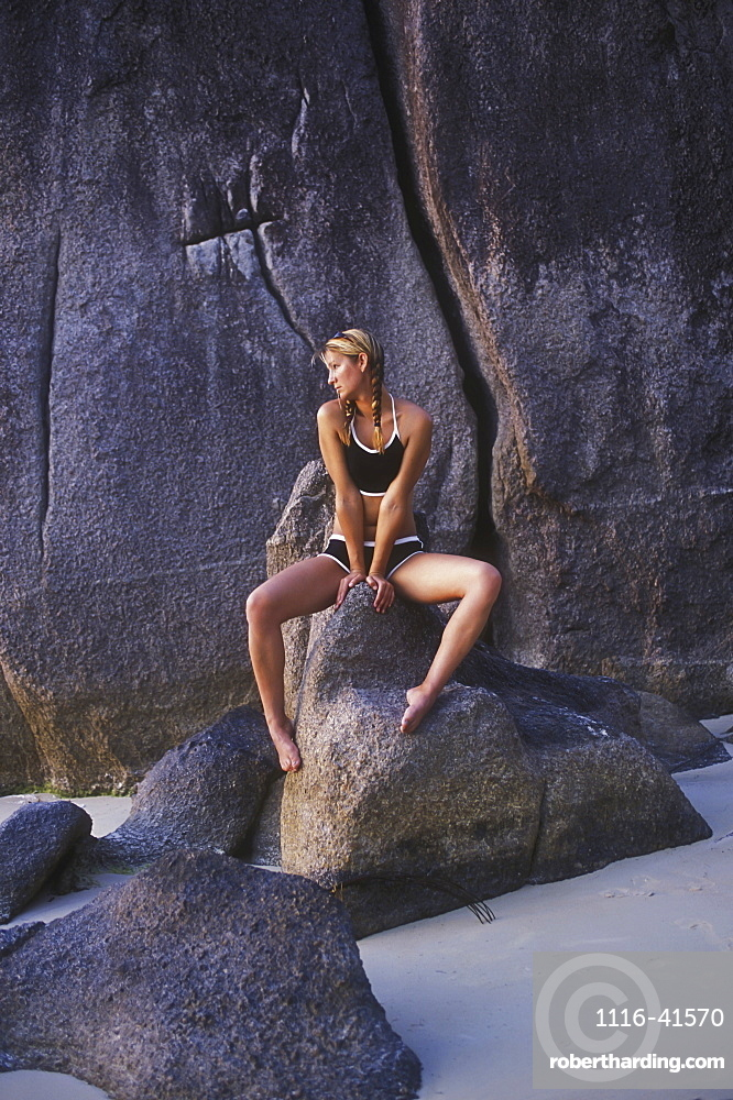 An Attractive Blond Haired Woman Sits On Rocks On The Beach Of A Tropical Island, Koh Tao, Thailand