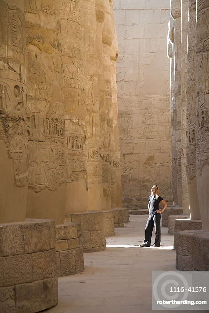 A Woman Tourist Stands At The Base Of The Massive Columns In The Temples Of Karnak On The East Bank Of Luxor Along The Nile River, Luxor, Egypt